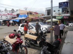 Hamdan petugas parkir di Lhokseumawe sedang melaksanakan tugasnya di jalan Gudang Lhokseumawe