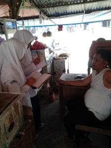 Tampak dua orang wartawan cilik tengah mewawancarai Bang Burhanuddin di pasar pagi Batuphat Lhokseumawe, Senin (5/10)